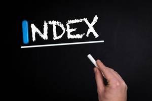 """Hand schreibt das Wort """"Index"""" mit Kreide auf eine schwarze Tafel"""