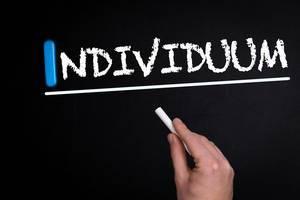 """Hand schreibt das Wort """"Individuum"""" mit Kreide auf eine schwarze Tafel"""