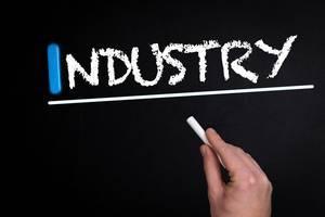 """Hand schreibt das Wort """"Industry"""" - Industrie - mit Kreide auf eine schwarze Tafel"""