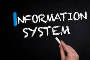 """Hand schreibt das Wort """"Informations-System"""" mit Kreide auf eine schwarze Tafel"""