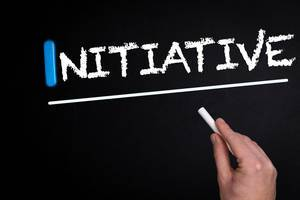 """Hand schreibt das Wort """"Initiative"""" mit Kreide auf eine schwarze Tafel"""