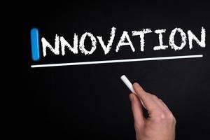 """Hand schreibt das Wort """"Innovation"""" mit Kreide auf eine schwarze Tafel"""