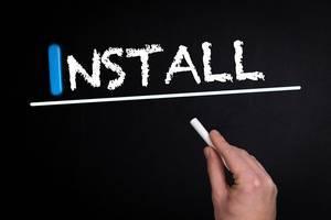 """Hand schreibt das Wort """"Install"""" - installieren / montieren - mit Kreide auf eine schwarze Tafel"""