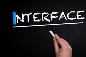 """Hand schreibt das Wort """"Interface"""" - Schnittstelle - mit Kreide auf eine schwarze Tafel"""