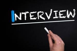 """Hand schreibt das Wort """"Interview"""" mit Kreide auf eine schwarze Tafel"""