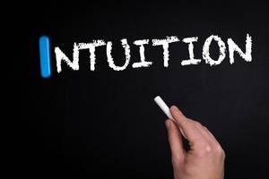"""Hand schreibt das Wort """"Intuition"""" mit Kreide auf eine schwarze Tafel"""