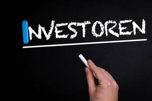 """Hand schreibt das Wort """"Investoren"""" mit Kreide auf eine schwarze Tafel"""