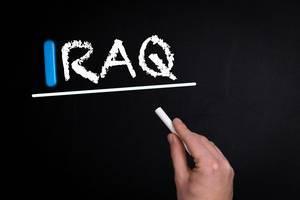 """Hand schreibt das Wort """"Iraq"""" mit Kreide auf eine schwarze Tafel"""