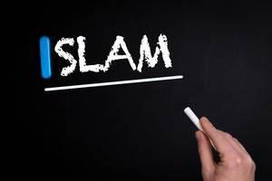 """Hand schreibt das Wort """"Islam"""" mit Kreide auf eine schwarze Tafel"""