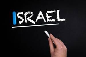"""Hand schreibt das Wort """"Israel"""" mit Kreide auf eine schwarze Tafel"""