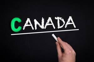 """Hand schreibt das Wort """"Kanada"""" mit Kreide auf eine schwarze Tafel"""
