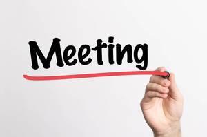"""Hand schreibt das Wort """"Meeting / Treffen"""" auf ein Whiteboard"""