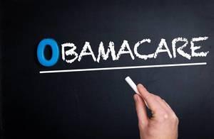 """Hand schreibt das Wort """"Obamacare"""" mit Kreide auf eine schwarze Tafel"""