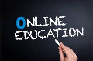 """Hand schreibt das Wort """"Online Education"""" - Online-Unterricht - mit Kreide auf eine schwarze Tafel"""