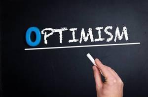 """Hand schreibt das Wort """"Optimism"""" mit Kreide auf eine schwarze Tafel"""