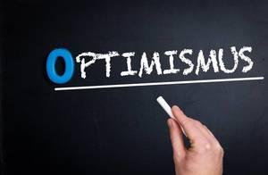 """Hand schreibt das Wort """"Optimismus"""" mit Kreide auf eine schwarze Tafel"""