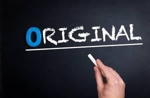 """Hand schreibt das Wort """"Original"""" mit Kreide auf eine schwarze Tafel"""