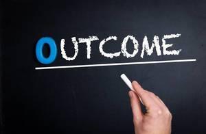 """Hand schreibt das Wort """"Outcome"""" - Ergebnis / Ausgang - mit Kreide auf eine schwarze Tafel"""