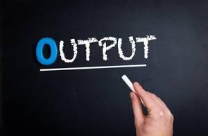 """Hand schreibt das Wort """"Output"""" - Ausgang / Leistung - mit Kreide auf eine schwarze Tafel"""