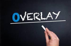 """Hand schreibt das Wort """"Overlay"""" mit Kreide auf eine schwarze Tafel"""