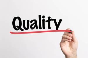 """Hand schreibt das Wort """"Qualität"""" auf ein Whiteboard"""