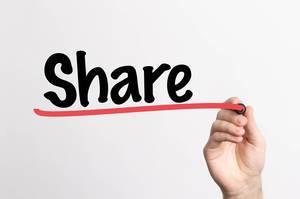 """Hand schreibt das Wort """"teilen"""" auf ein Whiteboard"""