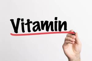 """Hand schreibt das Wort """"Vitamin"""" auf ein Whiteboard"""