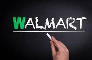 """Hand schreibt das Wort """"Walmart"""" mit Kreide auf eine schwarze Tafel"""
