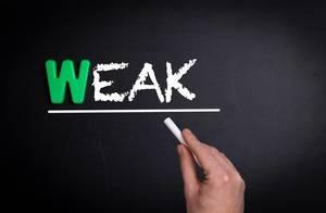 """Hand schreibt das Wort """"Weak"""" - Schwach - mit Kreide auf eine schwarze Tafel"""