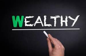 """Hand schreibt das Wort """"Wealthy"""" - Reich / Wohlhabend - mit Kreide auf eine schwarze Tafel"""