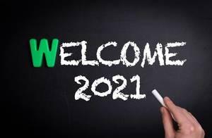 """Hand schreibt das Wort """"Welcome 2021"""" - Willkommen 2021 - mit Kreide auf eine schwarze Tafel"""