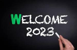 """Hand schreibt das Wort """"Welcome 2023"""" - Willkommen 2023 - mit Kreide auf eine schwarze Tafel"""