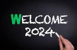 """Hand schreibt das Wort """"Welcome 2024"""" - Willkommen 2024 - mit Kreide auf eine schwarze Tafel"""