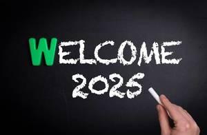 """Hand schreibt das Wort """"Welcome 2025"""" - Willkommen 2025 - mit Kreide auf eine schwarze Tafel"""