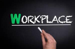 """Hand schreibt das Wort """"Workplace"""" - Arbeitsplatz - mit Kreide auf eine schwarze Tafel"""