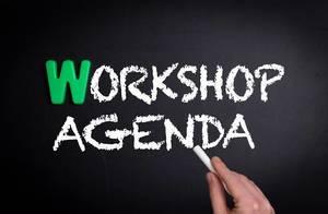 """Hand schreibt das Wort """"Workshop Agenda"""" - Workshop-Programm - mit Kreide auf eine schwarze Tafel"""
