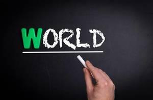 """Hand schreibt das Wort """"World"""" - Welt - mit Kreide auf eine schwarze Tafel"""