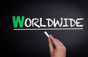 """Hand schreibt das Wort """"Worldwide"""" - weltweit - mit Kreide auf eine schwarze Tafel"""