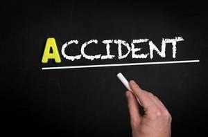"""Hand schreibt """"accident"""" auf schwarze Tafel"""
