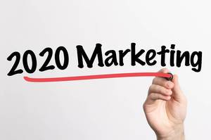 """Hand schreibt """"2020 Marketing"""" auf ein Whiteboard"""