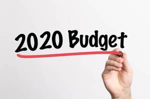 """Hand schreibt """"Budget für 2020"""" auf ein Whiteboard"""