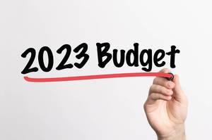 """Hand schreibt """"Budget für 2023"""" auf ein Whiteboard"""