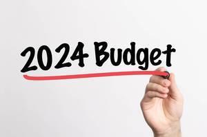 """Hand schreibt """"Budget für 2024"""" auf ein Whiteboard"""