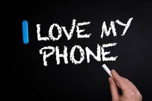 """Hand schreibt """"I love my phone"""" - Ich liebe mein Handy - mit Kreide auf eine schwarze Tafel"""