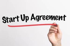 """Hand schreibt """"Start-up Vereinbarung"""" auf ein Whiteboard"""