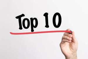 """Hand schreibt  """"TOP 10 / die besten 10"""" auf ein Whiteboard"""