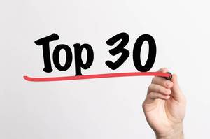 """Hand schreibt """"Top 30 / die besten 30"""" auf ein Whiteboard"""