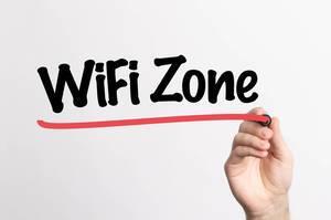 """Hand schreibt """"Wifi-Zone"""" auf ein Whiteboard"""