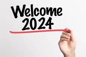 """Hand schreibt """"Willkommen 2024"""" auf ein Whiteboard"""