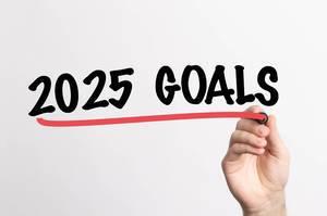 Hand schreibt Ziele für 2025 auf ein Whiteboard